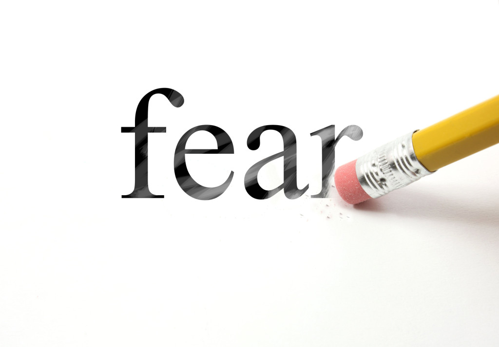 The word Fear written with a pencil on white paper.  An eraser from a pencil is starting to erase the word fear.